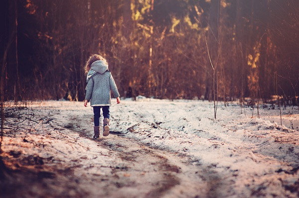 girl walking the road in winter forest