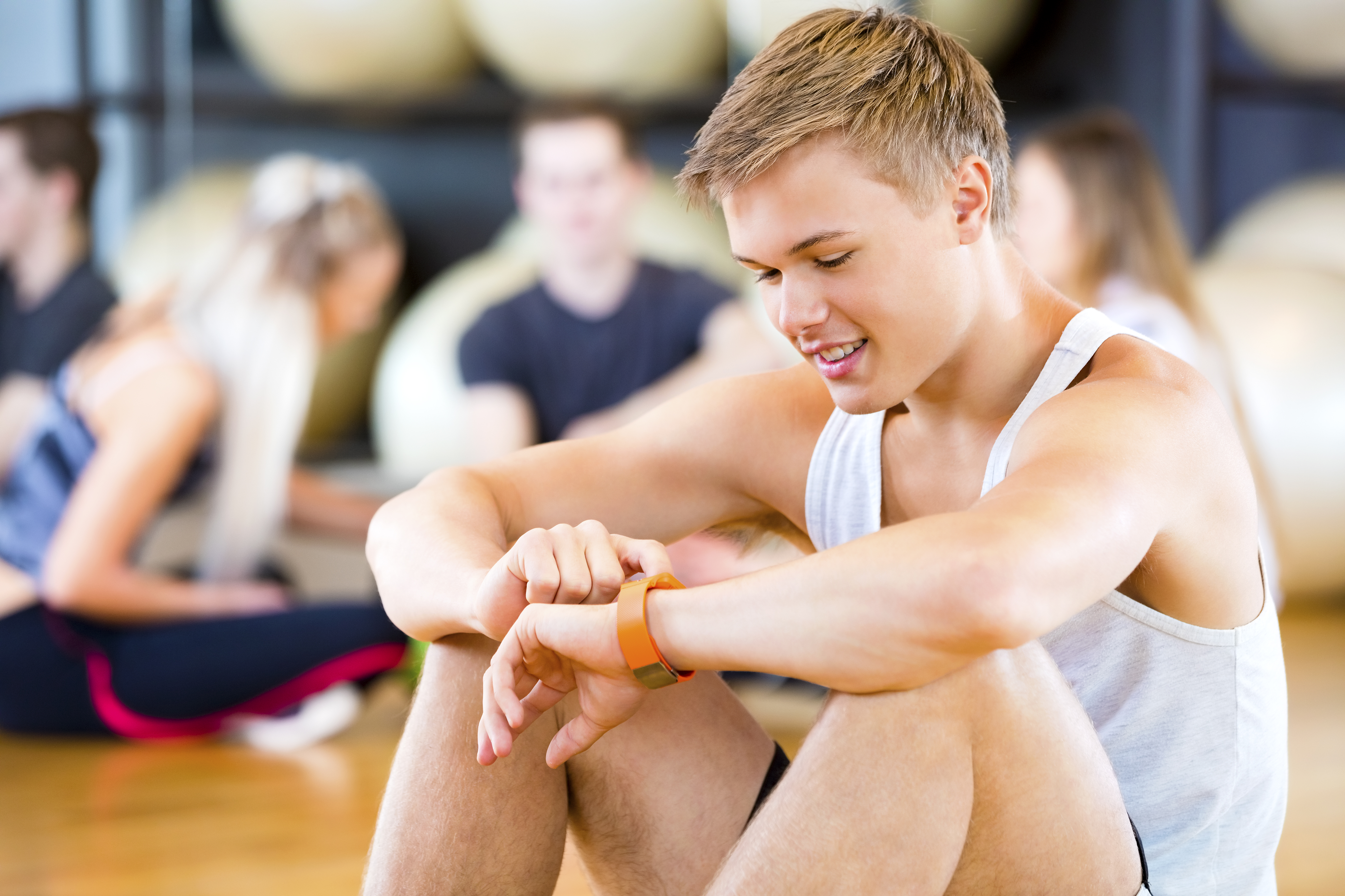 Teenager in Gym looking at Watch