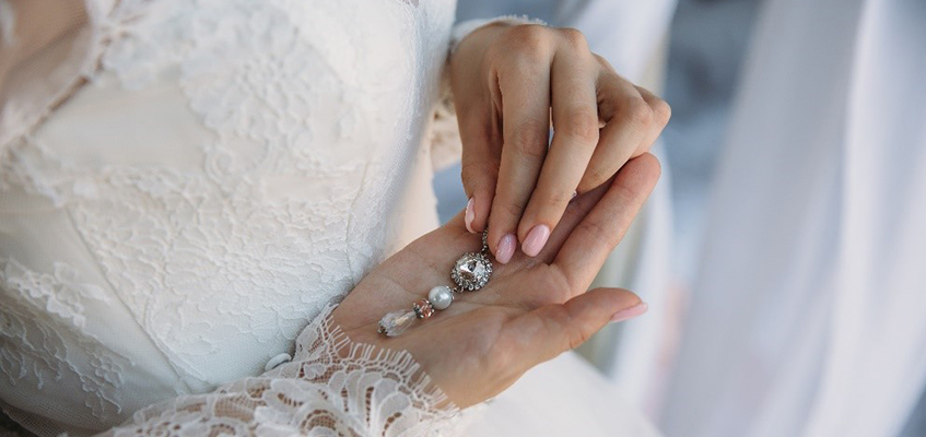 woman in wedding dress holding jewllery in her hand